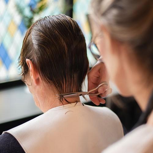 De haarpunten van de klant worden afgeknipt in knapsalon