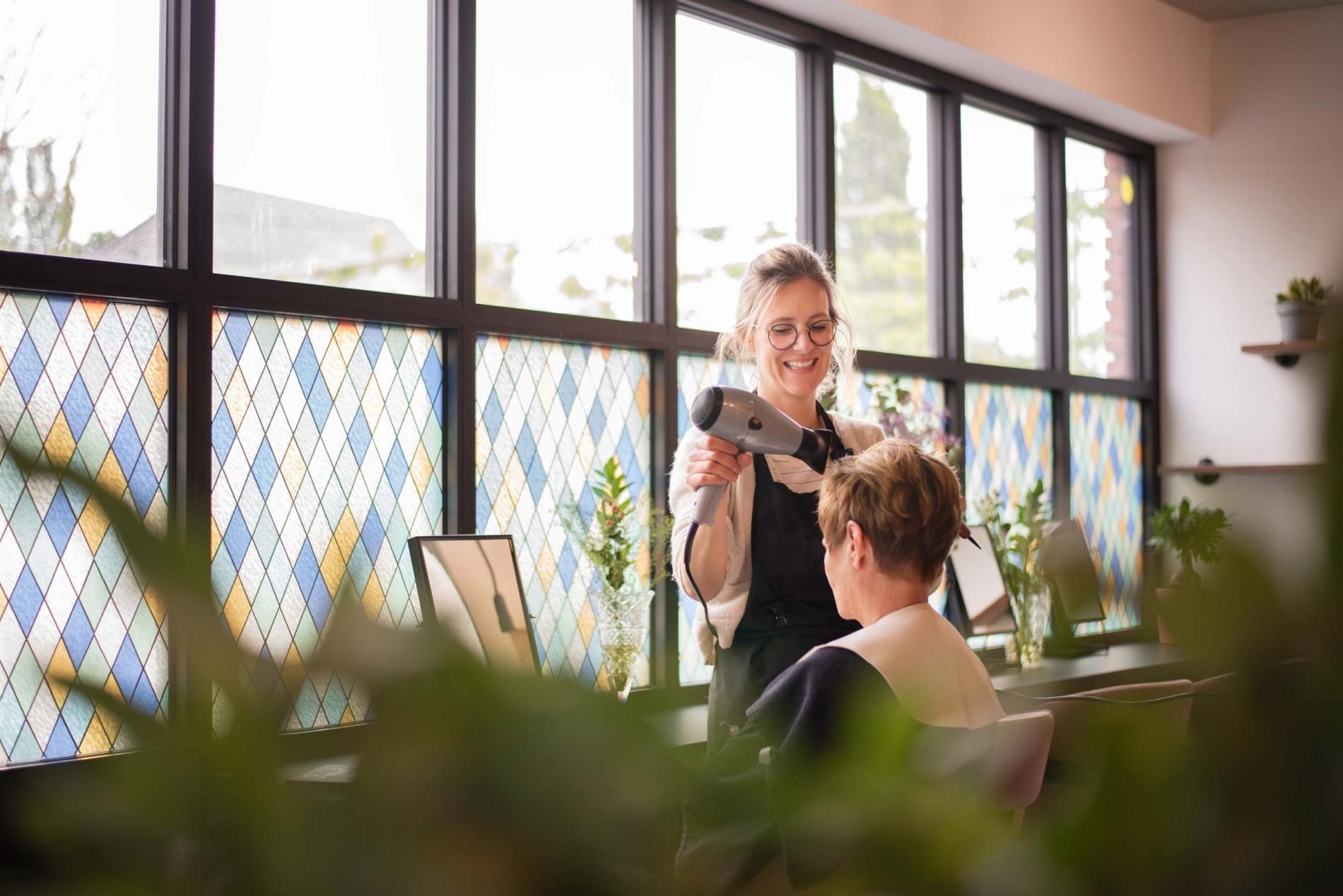 Lotte brusht het haar van haar klant in kapsalon